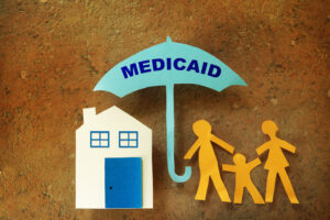 Paper cut-out out of family of three people and their home; under the umbrella protection of Medicaid